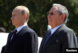 FILE - Russian President Vladimir Putin (L) stands next to Cuba's President Raul Castro as they attend a wreath-laying ceremony at the Soviet Soldier monument in Havana, July 11, 2014.