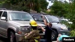 En esta imagen obtenida de un video en las redes sociales, se puede ver a personas ocultándose detrás de vehículos durante un tiroteo en Panama City, Florida. Facebook/Geraldine Rinaldi/ via Reuters. Mayo 22 de 2018.