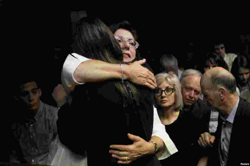 Relatives of Oscar Pistorius hug each other ahead of proceedings at the Pretoria magistrates court February 22, 2013.