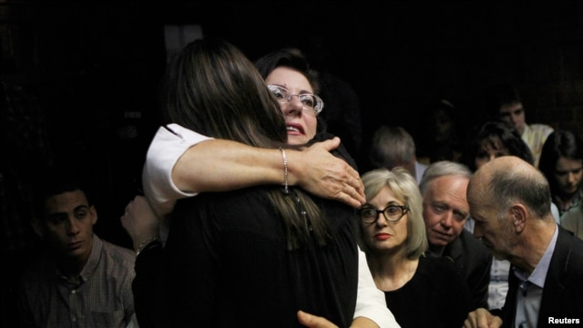 Relatives of Oscar Pistorius hug each other ahead of proceedings at the Pretoria magistrates court on Feb. 22, 2013.