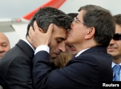 Turkish Prime Minister Ahmet Davutoglu (R) kisses Turkish Consul General of Mosul Ozturk Yilmaz on the forehead during a welcoming ceremony at Esenboga airport in Ankara, Sept. 20, 2014.