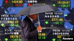 A pedestrian walks past a stock quotation board displaying various countries' share indices, outside a brokerage in Tokyo Oct. 1, 2013.
