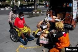 Sukarelawan Palang Merah Indonesia (mengenakan kostum wayang) membagikan makanan gratis, saat pemerintah melonggarkan pembatasan darurat di tengah pandemi COVID-19 di Solo, Jawa Tengah, 27 Juli 2021. (Antara Foto/Maulana S)