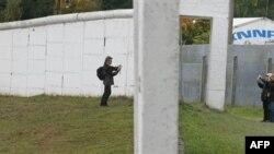 Du khách chụp ảnh cả 2 bên bức tường phân chia Ðông Ðức Tây Ðức trong ngôi làng Moedlareuth