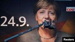 지난 14일 독일 뒤스부르크에서 24일 총선을 앞두고 앙겔라 메르켈 총리의 얼굴이 담긴 대형 포스터를 설치하고 있다.