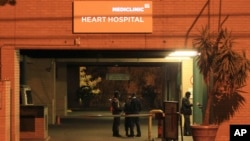 Police officers stand outside the main entrance of the Mediclinic Heart Hospital where former South African President Nelson Mandela is being treated in Pretoria, South Africa Sunday, Jun. 23, 2013.