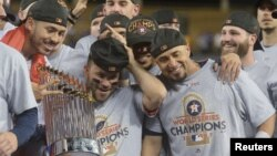 Houston Astros second baseman Jose Altuve celebrates with teammates and the Commissioner's Trophy after defeating the Los Angeles Dodgers in Game 7 of the 2017 World Series at Dodger Stadium, Los Angeles, Nov. 1, 2017. Gary A. Vasquez-USA TODAY Sports