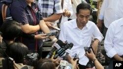 Presiden terpilih Joko Widodo berbicara dengan wartawan dalam kunjungannya ke Waduk Pluit di Jakarta (22/7). (AP/Dita Alangkara)
