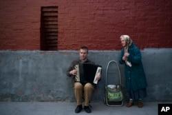 Un hombre toca el acordeón mientras una anciana canta previo al inicio de la Copa Mundial de la FIFA en Moscú el miércoles, 13 de junio de 2018.