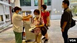 香港卫生署人员8月3日早上在港岛南区香港仔赛马会诊所,派发武汉肺炎病毒深喉唾液测试包,约100名市民清晨7时半前到场轮候。 (美国之音/汤惠芸)