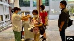 香港衛生署人員8月3日早上在港島南區香港仔賽馬會診所,派發武漢肺炎病毒深喉唾液測試包,約100名市民清晨7時半前到場輪候。(美國之音湯惠芸)