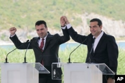 Greek Prime Minister Alexis Tsipras, right and his Macedonian counterpart Zoran Zaev, raise their hands during a signing agreement for Macedonia's new name in the village of Psarades, on June 17, 2018.