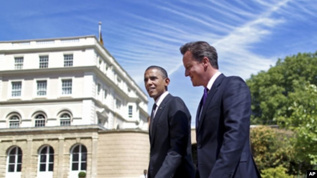 U.S. President Barack Obama and Britain's Prime Minister David Cameron walk in the gardens after holding a joint news conference at Lancaster House in London, May 25, 2011