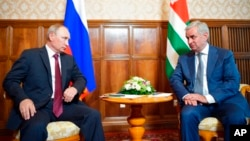 Russian President Vladimir Putin, left, and leader of Georgia's breakaway province of Abkhazia, Raul Khadzhimba, talk during their meeting in the provincial town of Pitsunda, Aug. 8, 2017.