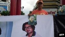 Các nhà hoạt động Trung Quốc cầm hình ông Chu Ngu Phù (dưới) và Lưu Hiểu Ba trong cuộc biểu tình tại Bangkok, Thái Lan