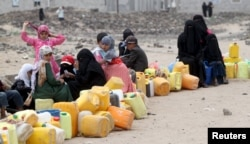 FILE - A five-day humanitarian truce in Yemen appeared to be broadly holding as people wait to collect water from a public tap amidst an acute water shortage, in Sana'a, May 13, 2015.