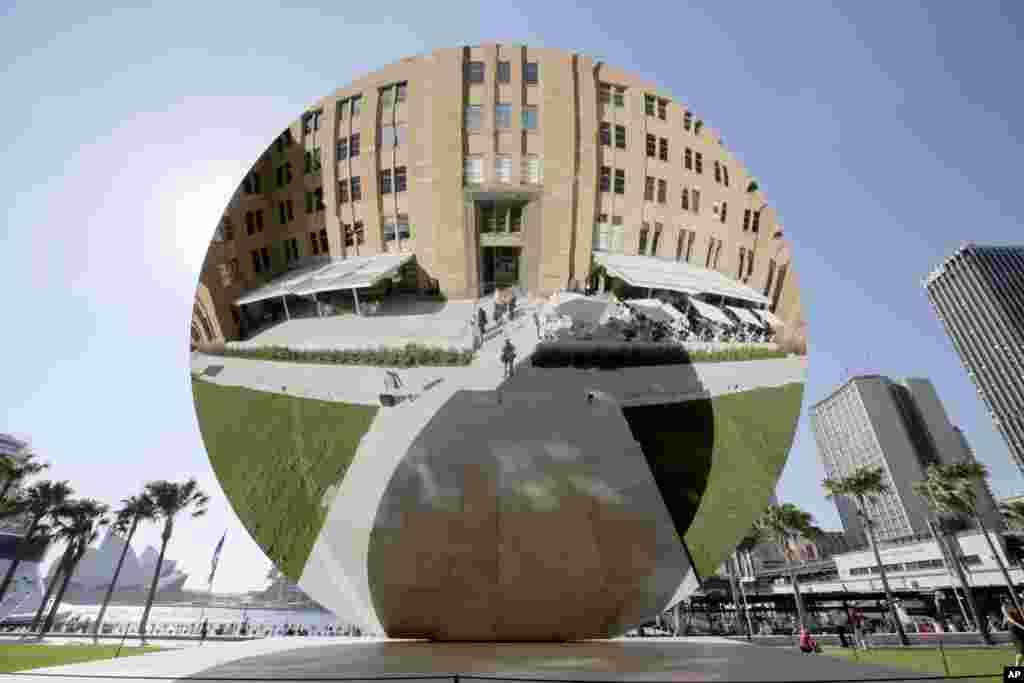 """Một đĩa bằng thép không rỉ rộng 10 mét có tên """"Gương Trời,"""" tác phẩm nghệ thuật của nghệ sĩ Anh Anish Kapoor, được trưng bày tại Viện Bảo Tàng nghệ thuật đương đại ở Sydney, Australia. Tấm gương có những mặt lồi lõm tạo ra những hình ảnh thay đổi liên tục khi mặt trời và mây di chuyển hoặc khi có người đi ngang."""