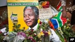 Warga Afrika Selatan meletakkan karangan bunga di depan bekas rumah Nelson Mandela di Soweto, Johannesburg, Afrika Selatan (7/12).