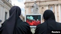 一群天主教修女正在梵蒂岡聖伯多祿廣場的大電視螢幕觀看特別彌撒的進行過程