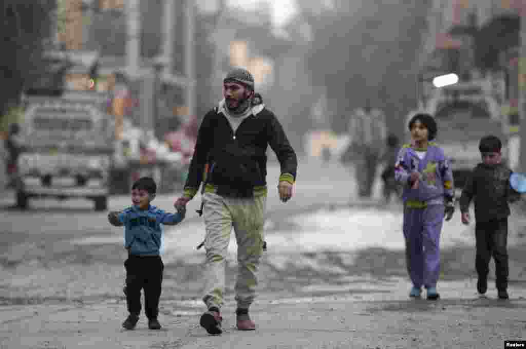 A Free Syrian Army fighter holds the hand of his son as they walk along a street in Deir al-Zor, Feb. 10, 2014.