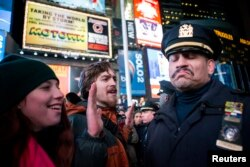 FILE - An NYPD officer, right, reacts to demonstrators protesting the July chokehold death of Eric Garner, in New York, Dec. 3, 2014. A grand jury returned no indictment against white officers in his death.