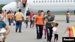 Mujeres y niños salen de un avión estadounidense en el que fueron transportados hasta el aeropuerto Ramón Villeda de San Pedro Sula, Honduras.