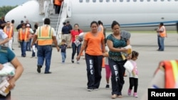 Women and children walk on the tarmac after being deported from the U.S., at the Ramon Villeda international airport in San Pedro Sula, in this July 14, 2014 handout provided by the Honduran Presidential House.
