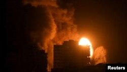 Asap dan kobaran api membubung dari sebuah gedung saat serangan udara oleh Israel di tengah peningkatan kekerasan antara Israel dan Palestina, Senin, 17 Mei 2021. (Foto: Ibraheem Abu Mustafa/Reuters)