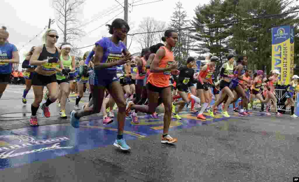 Runners cross the start line in the women's division of the Boston Marathon, in Hopkinton, April 20, 2015.