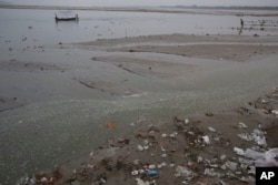 FILE - Plastic bags and garbage litter the banks of River Ganges on World Environment Day in Allahabad, India, June 5, 2017.
