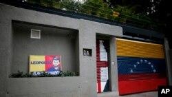 资料照片-刚获释的委内瑞拉反对派领导人洛佩斯手持国旗在加拉加斯的住所外向支持者致意