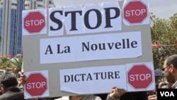 "Seorang pendukung rejim lama Tunisia memajang spanduk yang bertuliskan ""Hentikan Kediktatoran Baru"" dalam demonstrasi menentang pemilu-pemilu mendatang."