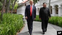 Le président américain Donald Trump et le dirigeant nord-coréen Kim Jong-Un marchent au sortir d'un déjeuner à l'hôtel Capella sur l'île de Sentosa à Singapour, le 12 juin 2018 (AP Photo/Evan Vucci).