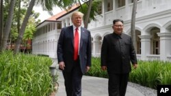 FILE - U.S. President Donald Trump and North Korea leader Kim Jong Un walk from their lunch at the Capella resort on Sentosa Island in Singapore, June 12, 2018.