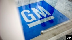 FILE -The logo for General Motors decorates the entrance at the site of a GM information technology center in Roswell, Georgia.