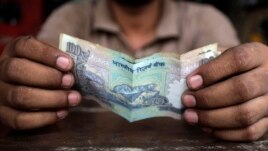 FILE - A cashier holds an Indian rupee.