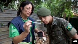 A health agent from Sao Paulo's Public health secretary shows an army soldier Aedes aegypti mosquito larvae that she found during clean up operation against the insect, which is a vector for transmitting the Zika virus, in Sao Paulo, Brazil, Jan. 20, 2016