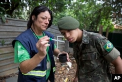 FILE - A health agent from Sao Paulo's Public health secretary shows an army soldier Aedes aegypti mosquito larvae that she found during clean up operation against the insect, which is a vector for transmitting the Zika virus, in Sao Paulo, Brazil, Jan. 20, 2016