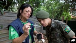 A health agent from Sao Paulo's Public health secretary shows an army soldier Aedes aegypti mosquito larvae that she found during clean up operation against the insect, which is a vector for transmitting the Zika virus, in Sao Paulo, Brazil, Jan. 20, 2016.