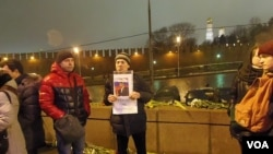 涅姆佐夫的一名支持者在他遇害的大桥上手举标语:英雄不死。(美国之音白桦拍摄)