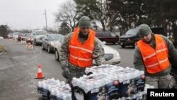 密西根州国民卫队成员向开车排队的弗林特居民分发瓶装水。(2016年1月21日)