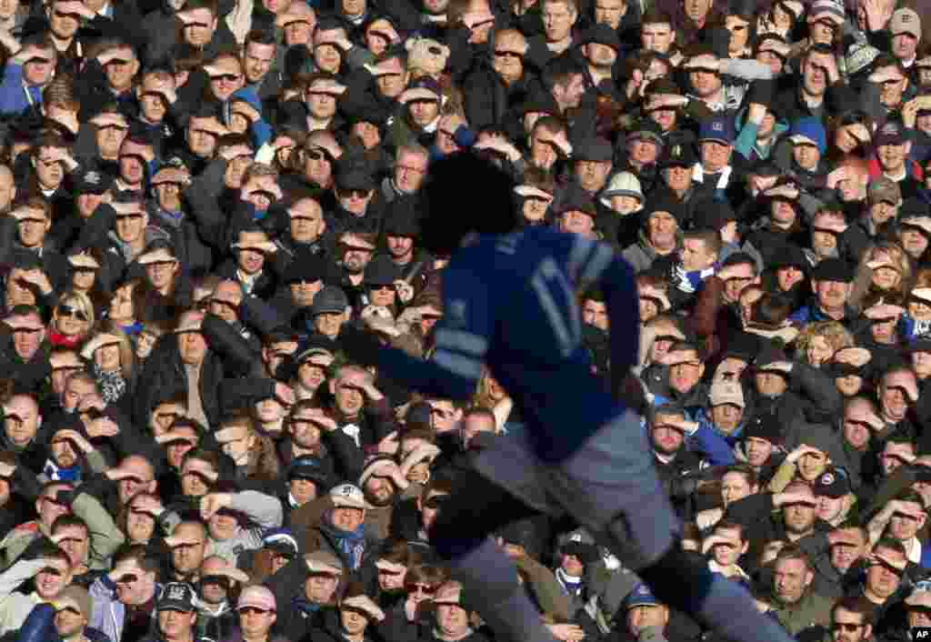 Supporters shield their eyes from the sun as Everton play Southampton during the English Premier League soccer match at Goodison Park Stadium, Liverpool, England.