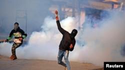 Seorang demonstran melemparkan batu ke tengah asap akibat tembakan gas air mata polisi India saat berunjuk rasa di Kashmir, Srinagar, 13 Januari 2018.