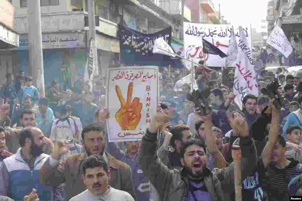 "Demonstrators hold a placard that reads ""Victory sign over the palace,"" during a protest against Syria's President Bashar al-Assad after Friday prayers in Binsh, November 30, 2012."