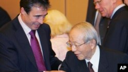 Le Premier ministre danois Anders Fogh Rasmussen, à gauche, assiste le président de Toyota Motor Co., Tatsuro Toyoda, qui tente de lui serrer la main après une séance photo lors de sa visite au siège du principal constructeur automobile japonais à Toyoda,