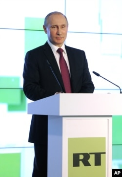 FILE - Russian President Vladimir Putin speaks as he attends an exhibition marking the 10th anniversary of RT's (formerly Russia Today) 24-hour English-language TV news channel in Moscow, Russia, Dec. 10, 2015.