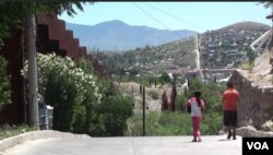 Two kids by the border wall in Nogales, Mexico. (G. Flakus/VOA)