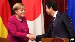 아베 신조 일본 총리(오른쪽)와 앙겔라 메르켈 독일 총리가 4일 도쿄 총리 관저에서 정상회담을 가진 후 기자회견을 열고 악수하고 있다.