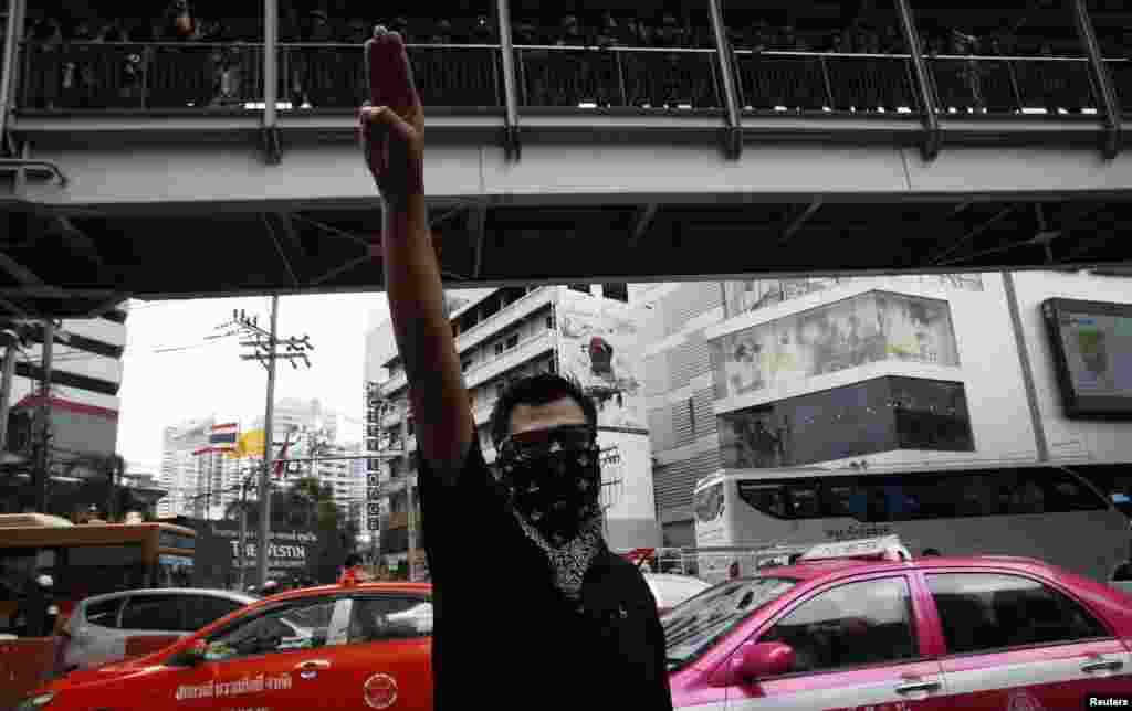 A protester against military rule gestures by holding up his three middle fingers in the air, as soldiers look on from an elevated walkway, during a brief demonstration outside a shopping mall in Bangkok, June 1, 2014.