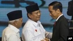 Calon-calon presiden Joko Widodo dan Prabowo Subianto, bersama calon wakil presiden Prabowo, Hatta Rajasa usai debat di Jakarta (9/6). (AP/Dita Alangkara)